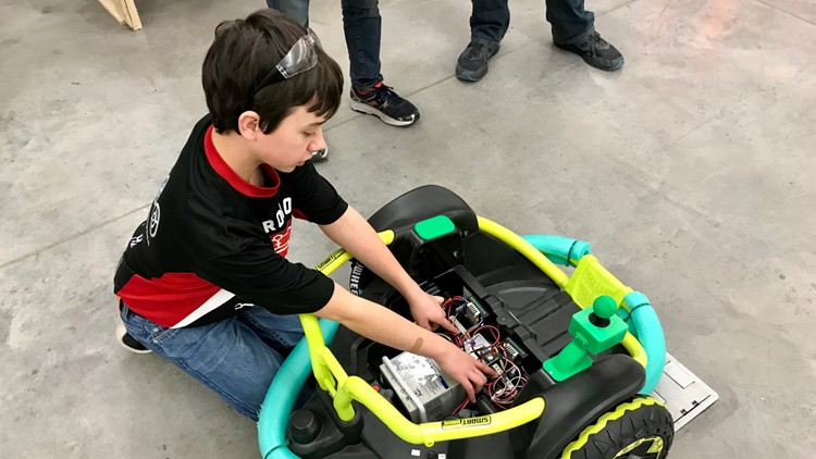 Farmington High School Robotics Team member Alex Treakle points out the electrical components he replaced in the Power Wheels toy that became Cillian Jackson's power wheelchair.