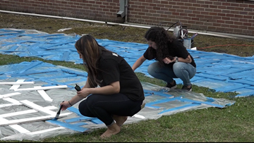 Volunteers paint blue crosses for child abuse awareness
