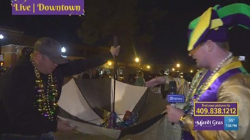 Mardi Gras Highlights | Man collects beads with upside-down umbrella in downtown Beaumont parade