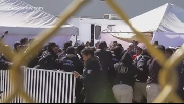 Confrontation erupts as migrants try to break past barriers placed by Mexican authorities