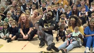 Saints linebacker surprises students with pizza, 'Children of God' headbands