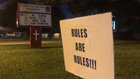 'Rules are Rules' signs appear outside school at center of 'hair-braid extension' controversy