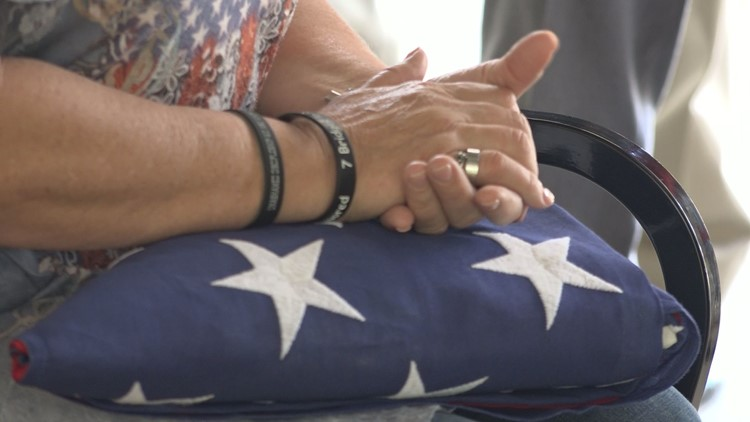 DeLayne Davis accepts the American Flag for Lt. Butterfield at unclaimed remains service